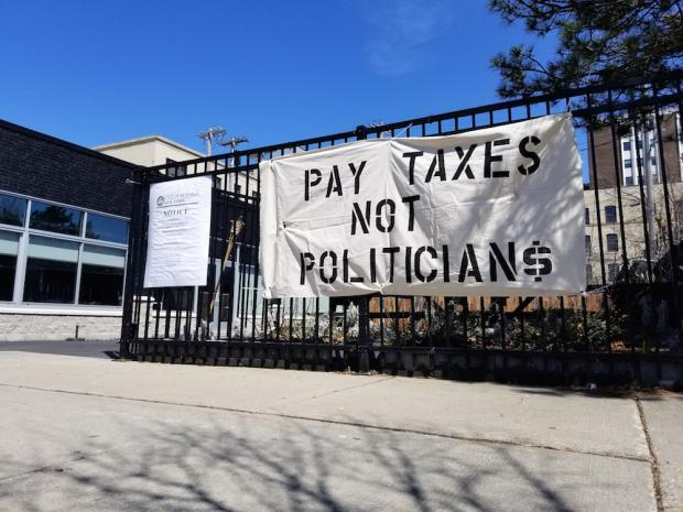 A banner dropped Thursday afternoon at the northeast corner of Elmwood and Bryant. Photo by Johanna C. Dominguez.