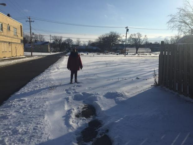 Marva Threat on Detroit Street, where her property line ends and the uncleared, city-owned sidewalk begins.